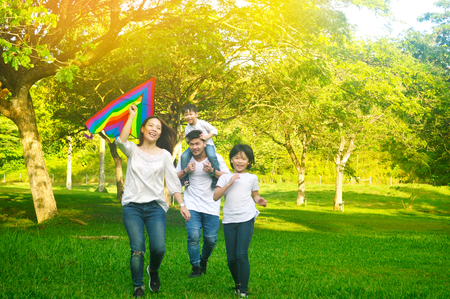 Photo pour Outdoor portrait of asian parent flying kite and kids - image libre de droit
