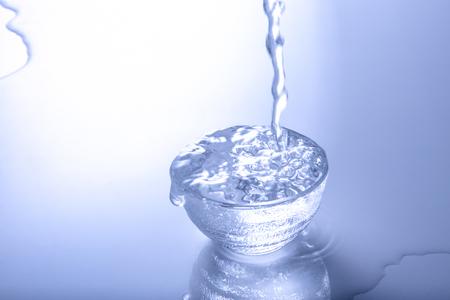 Foto de Sake pouring into overflowing glass - Imagen libre de derechos