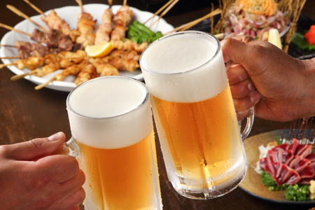 Photo pour Japanese young people hands toasting and cheering beer mugs - image libre de droit