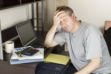 Photo pour Mature man holding head in hand with computer, calculator, tax income booklet and coffee cup on desk - image libre de droit