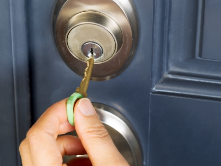 Foto de female hand putting house key into front door lock of house - Imagen libre de derechos