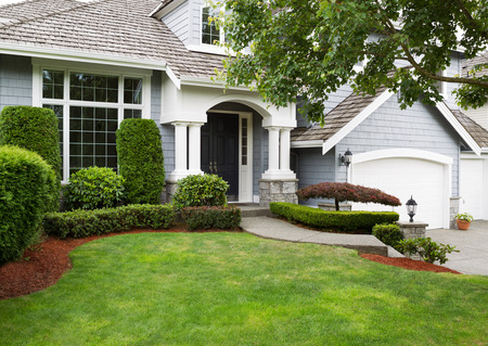 Foto de Newly painted exterior of a North American home during summertime with green grass and flower beds  - Imagen libre de derechos