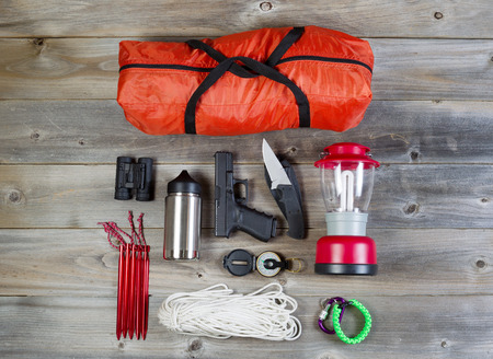 Foto de Overhead view of hiking gear and personal protection, pistol and knife, placed on rustic wood - Imagen libre de derechos