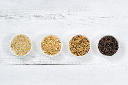 Foto de Top view of various rice types each within a small bowl on white wood - Imagen libre de derechos