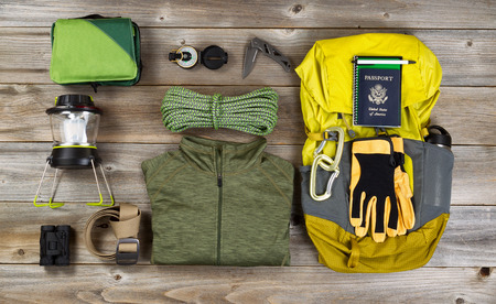 Photo pour High angled view of organized hiking gear for climbing placed on rustic wooden boards. - image libre de droit