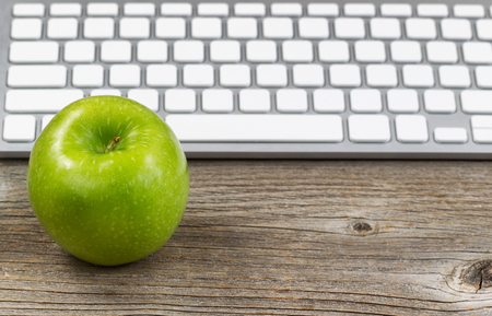 Foto de Selective focus on ripe green apple with partial keyboard in background. Layout in horizontal format on rustic wood. - Imagen libre de derechos