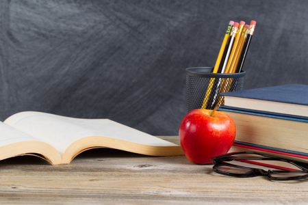 Foto de Desktop with books, red apple, reading glasses, and pencils in front of blackboard. Layout in horizontal format with plenty of copy space. - Imagen libre de derechos