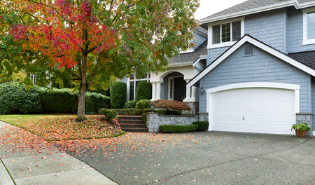 Photo for Front view of modern residential home during early autumn season in Northwest of United States. Maple trees beginning to change leaf colors. - Royalty Free Image