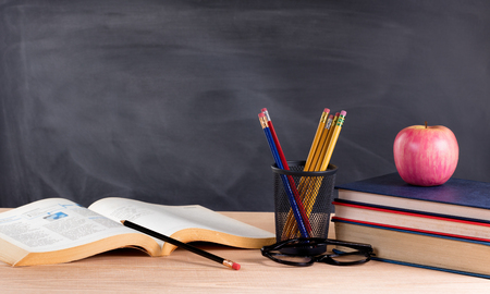 Photo pour Desktop with books, pencils, apple, reading glasses and blank blackboard in background. Selective focus on front part of desk objects. - image libre de droit