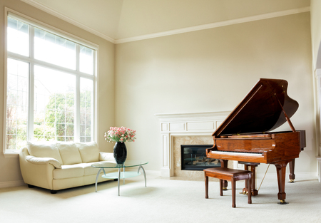 Photo pour Living room with grand piano, fireplace, sofa and large window with bright daylight coming through. - image libre de droit