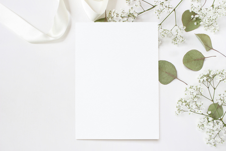 Foto für Styled stock photo. Feminine wedding desktop stationery mockup with blank greeting card, babys breath Gypsophila flowers, dry green eucalyptus leaves, satin ribbon and white background. Empty space. Top view. Picture for blog. - Lizenzfreies Bild
