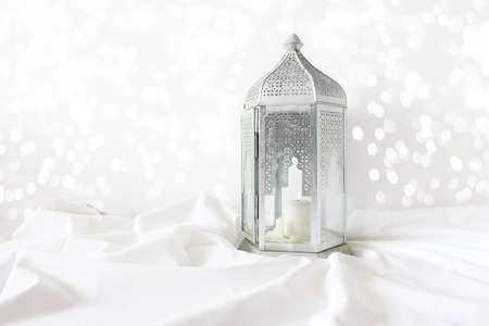 Photo for Ornamental silver Moroccan, Arabic lantern on white linen throw. Burning candle, glittering bokeh lights. Greeting card for Muslim community holy month Ramadan Kareem. Festive background. - Royalty Free Image