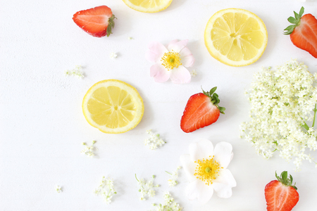 Foto de Styled stock photo. Summer fruit composition. Closeup of sliced lemons, elderflowers, strawberries and wild roses isolated on white wooden table background. Food pattern. Flat lay, top view. - Imagen libre de derechos