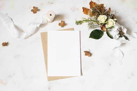 Photo pour Feminine winter wedding, birthday stationery mock-up scene. Blank greeting card, envelope. Dry hydrangea, white roses and gypsophila flowers bouquet. Marble stone table background. Flat lay, top view. - image libre de droit