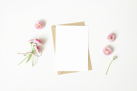 Photo for Feminine stationery, desktop mock-up scene. Vertical blank greeting card, craft paper envelope and daisy bouquet and flowers isolated on white table background. Flat lay, top view. Rustic composition. - Royalty Free Image