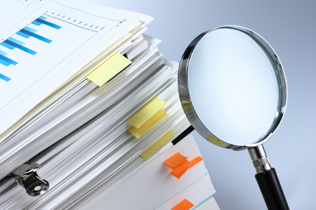 Photo for Investigate and analyze  Magnifying glass and stack of documents  - Royalty Free Image