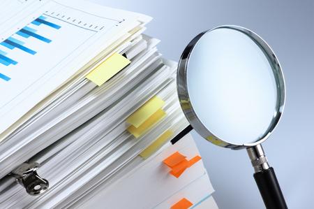 Foto de Investigate and analyze  Magnifying glass and stack of documents  - Imagen libre de derechos