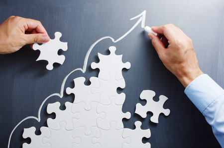 Photo pour Working on steps shaped jigsaw puzzle. Drawing up arrow on blackboard. Concept image of making growth strategy. - image libre de droit