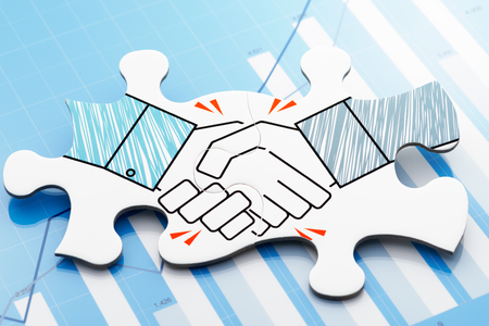Photo pour Handshake jigsaw puzzle pieces on blue chart. Concept image of business partnership and agreement. - image libre de droit