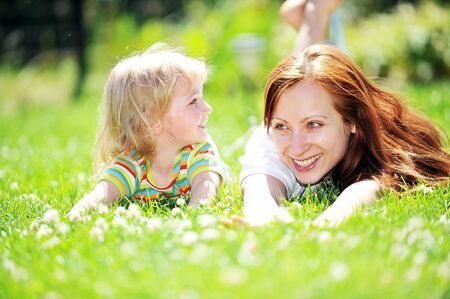 Photo for Beautiful young mother with her  daughter lie on grass . summer. - Royalty Free Image