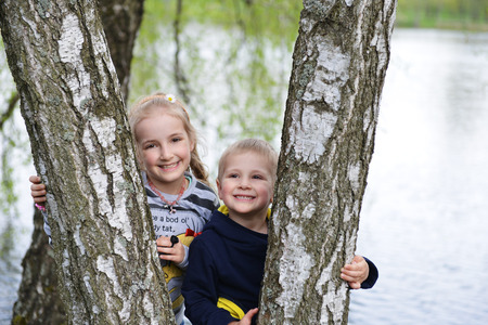 girl and her younger brother near tree in park