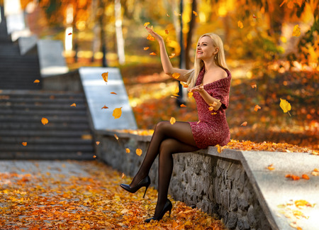Photo pour Beautiful blonde girl with perfect legs playing with fallen leaves on the street of autumn park in the lights of setting sun. - image libre de droit