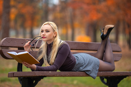 Photo for Beautiful student girl with perfect legs laying on the bench and reading the book in the autumn park in the lights of setting sun. - Royalty Free Image