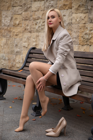 Photo for Beautiful girl in the coat with perfect legs sitting on the bench in the autumn park. - Royalty Free Image