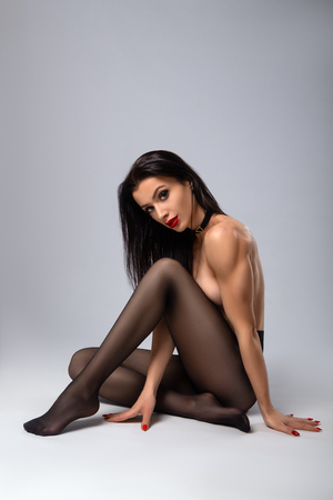 Foto de Beautiful sexy fitness woman with perfect sport shapes posing nude in pantyhose on the grey background. Sport fitness and health care issues. - Imagen libre de derechos