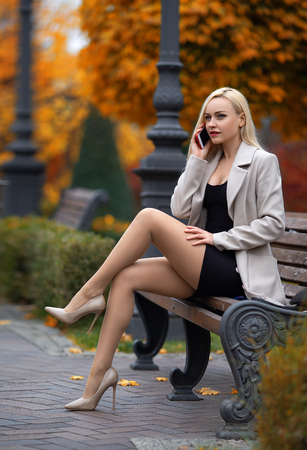 Photo pour Beautiful girl in the coat with perfect legs sitting on the bench and calling via mobile phone in the autumn park. - image libre de droit