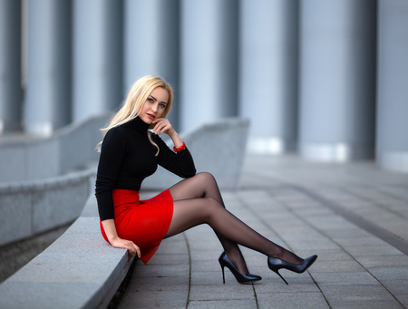 Photo pour Beautiful blonde girl in red skirt with perfect legs in pantyhose and shoes with high heels posing outdoor on the city square. - image libre de droit