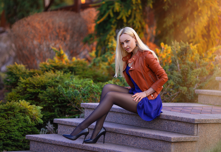 Photo for Beautiful blonde girl with perfect legs posing outdoor on the street of spring park in the lights of setting sun. - Royalty Free Image