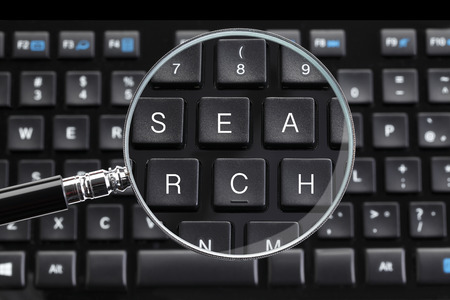 Photo pour Search written on keyboard with magnifying glass - image libre de droit