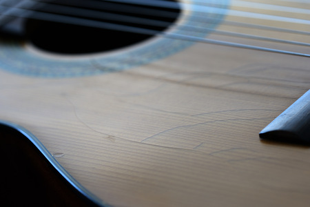 Photo for Old acoustic guitar with cracks on the soundboard close up - Royalty Free Image