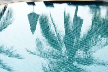 Foto de Reflections of palm trees and beach umbrellas in the pool in the morning. Blurred abstract background - Imagen libre de derechos
