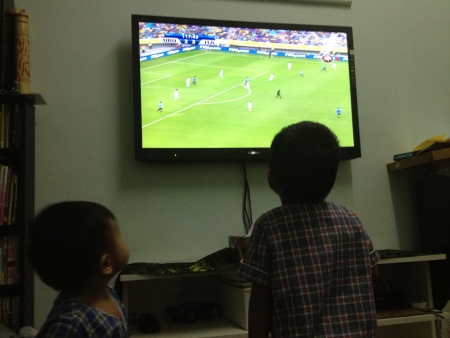 Children watching football game on television