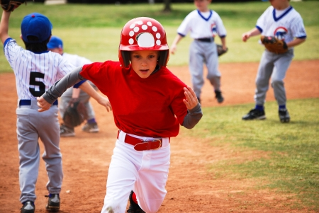 Youth little league baseball boy running bases.
