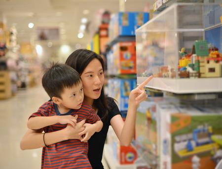 Foto de Young Asian mother and her kid shopping toy in shopping mall - Imagen libre de derechos