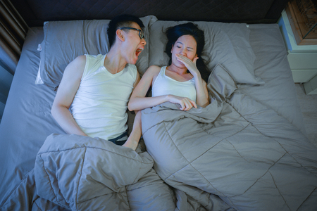 Photo pour Asian couple with bad breath issues on bed at night - image libre de droit