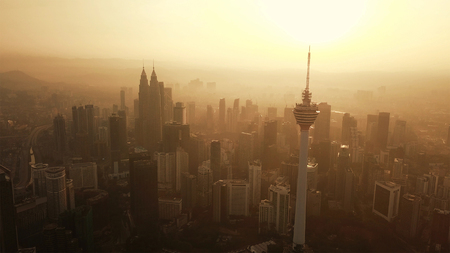 Photo pour Menara Kuala Lumpur Tower with the sun. Aerial view of Kuala Lumpur Downtown, Malaysia. Financial district and business centers in urban city in Asia. Skyscraper and high-rise buildings at sunset. - image libre de droit