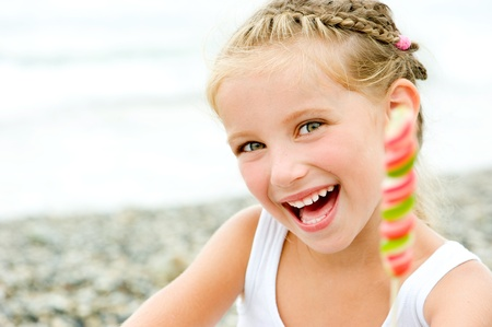 Photo for smily little girl with a candy on tropical beach vacation - Royalty Free Image