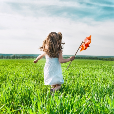 Foto de cute little girl on grass in summer day holds windmill in hand - Imagen libre de derechos