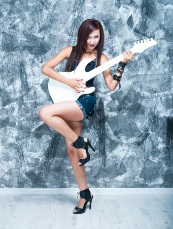 Photo for Beautiful rock singer with a white guitar in the studio - Royalty Free Image