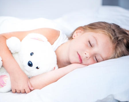 Photo pour little girl sleeping in white bed - image libre de droit