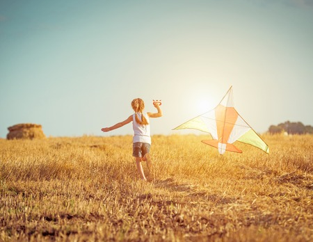 Photo pour happy little girl with a kite in a field - image libre de droit