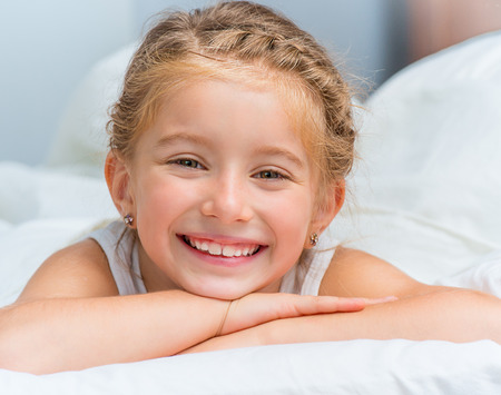 Foto per cute smiling little girl woke up in white bed - Immagine Royalty Free