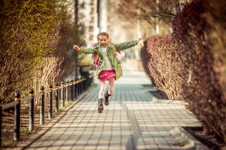 Photo pour happy little girl running home from school - image libre de droit