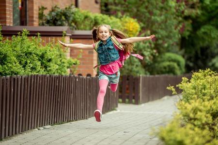 Foto de little girl with a backpack run from school - Imagen libre de derechos