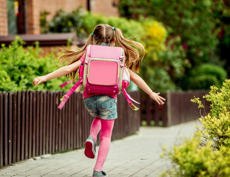 Foto de little girl with a backpack run  to school. back view - Imagen libre de derechos