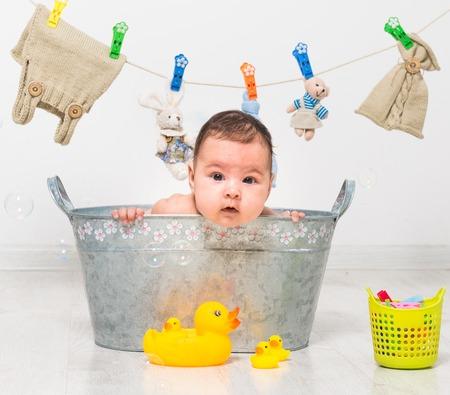 Photo pour little two-month girl bathes in a  trough and dry her clothes - image libre de droit